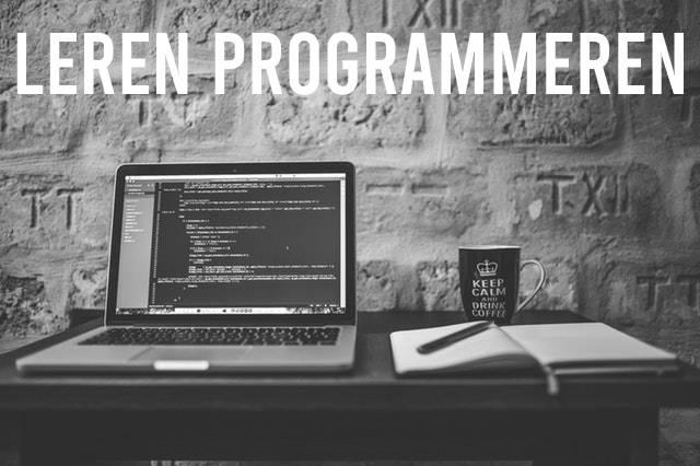 Leren programmeren: Laptop en schrift op bureau
