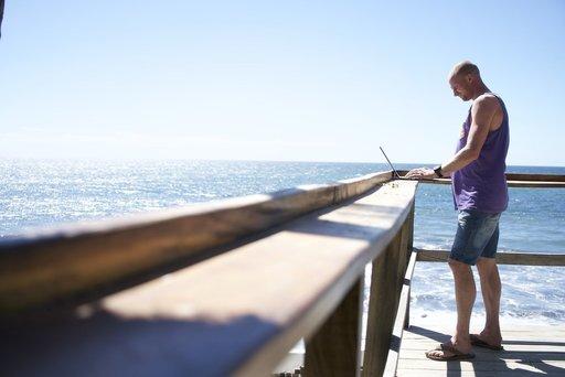 Werken en reizen met laptop aan zee