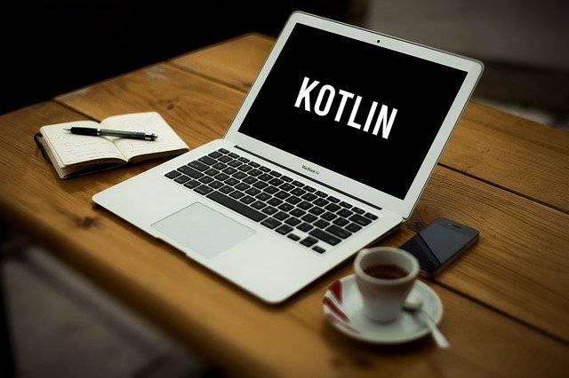 Laptop op bureau met Kotlin erop + koffie en kladblokje